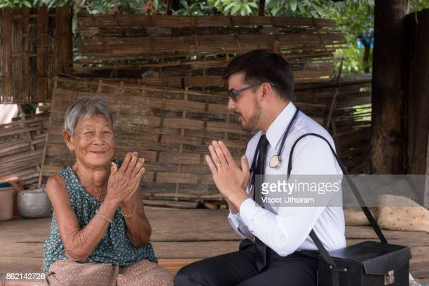 male doctor listening heart beat and breathing of elderly woman with stethoscope with first aid medical box. - morbillivirus stock pictures, royalty-free photos & images