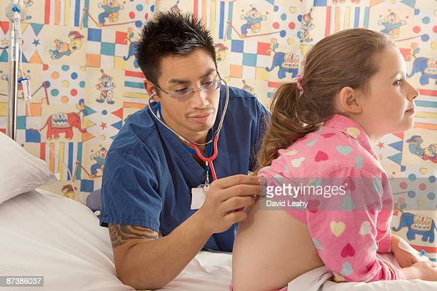 A male doctor listens to a girls back