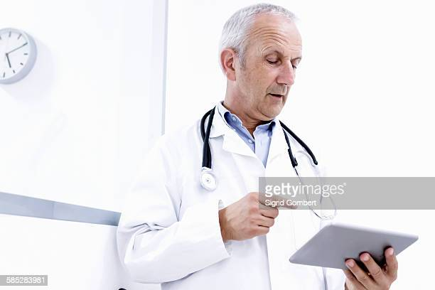 male doctor looking at digital tablet - sigrid gombert stockfoto's en -beelden