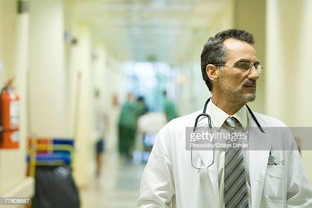 Male doctor looking away, hospital corridor in background