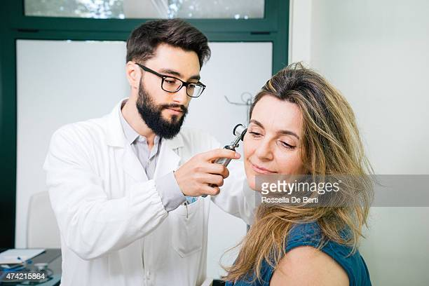 male doctor making ear exam - ear exam stock photos and pictures
