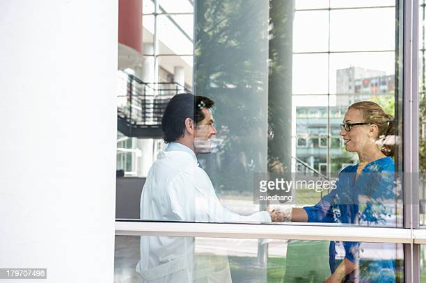 Male doctor meeting female colleague