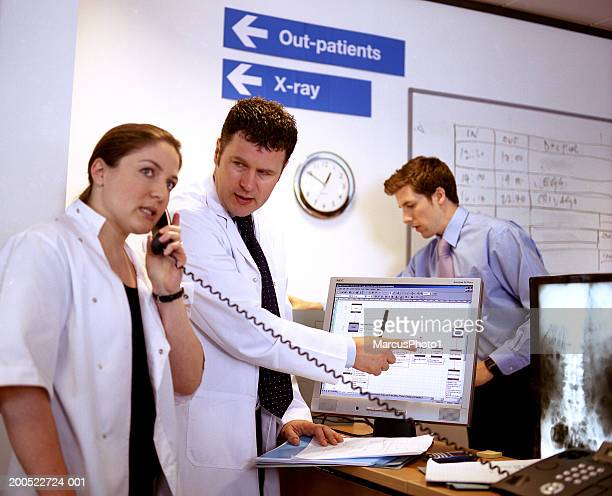 Male doctor pointing out computer screen to woman using telephone