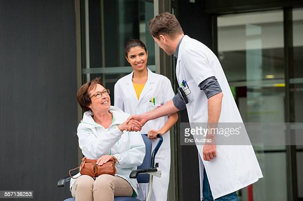 Male doctor shaking hands with a female patient sitting in a chair