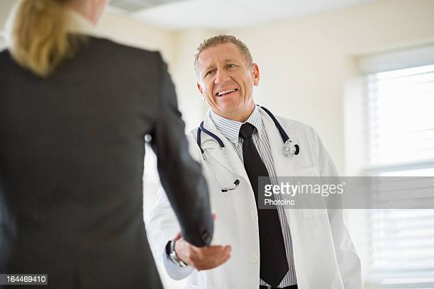 male doctor shaking hands with businesswoman - salesman stock pictures, royalty-free photos & images