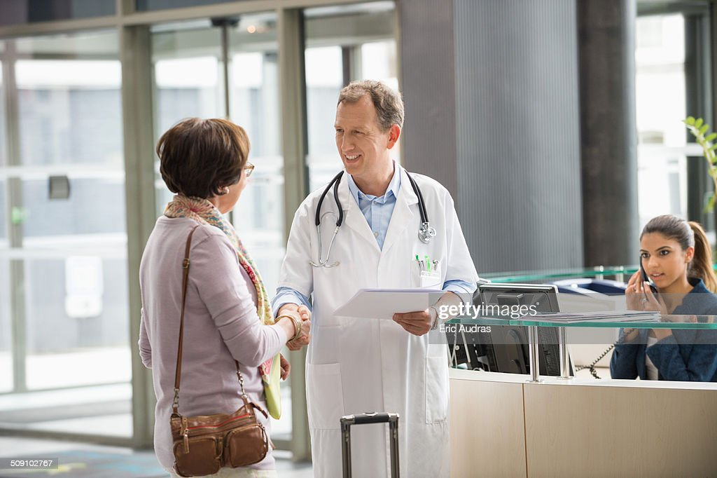 Male doctor shaking hands with his patient at hospital reception desk : Stock Photo