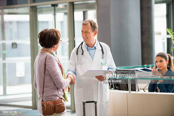 male doctor shaking hands with his patient at hospital reception desk - medical receptionist uniforms stock photos and pictures