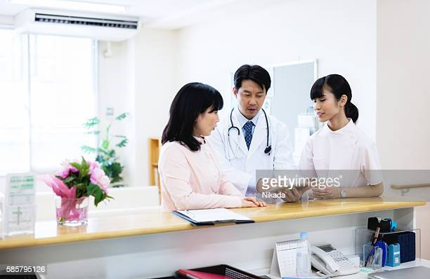 Male doctor showing digital tablet to patient