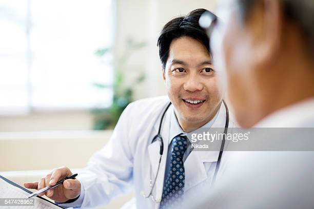 Male doctor showing record and explaining senior patient