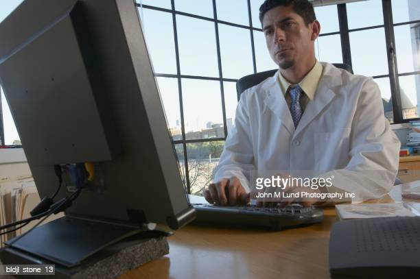 Male doctor sitting in his office working on a computer