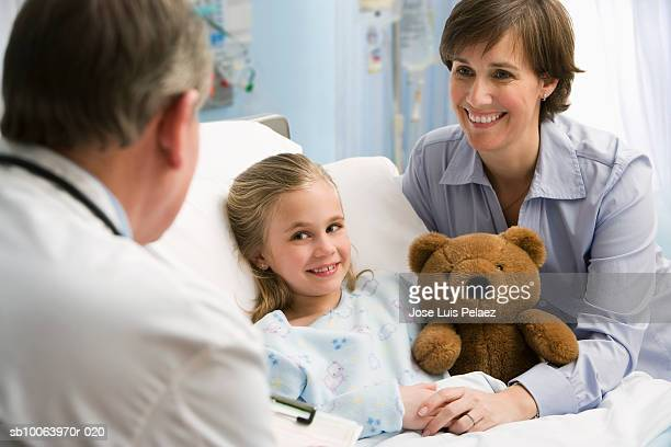 Male doctor smiling at mother and girl (6-7) holding teddy bear