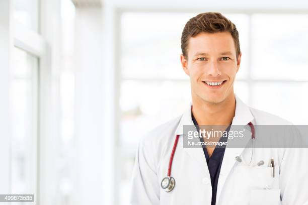 male doctor smiling in hospital - handsome doctors stock pictures, royalty-free photos & images