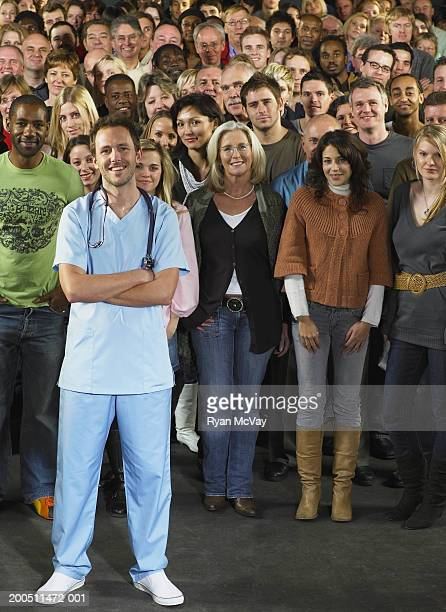male doctor standing in front of crowd, smiling, portrait - hero stock photos and pictures