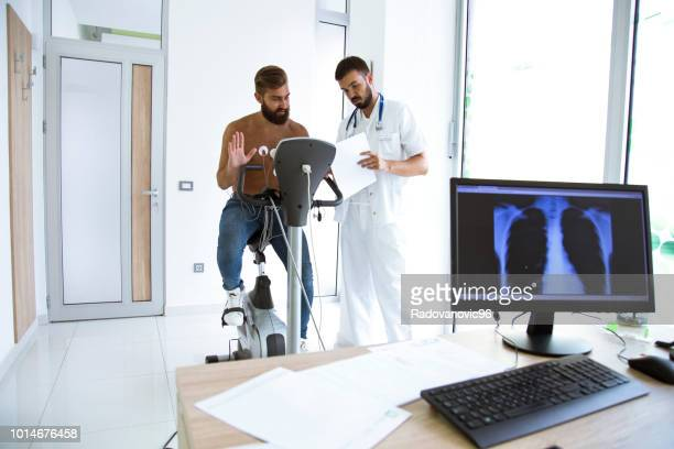 male doctor talking to male patient in hospital - heart disease stock pictures, royalty-free photos & images