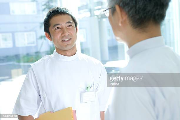 Male doctor talking to mature male doctor