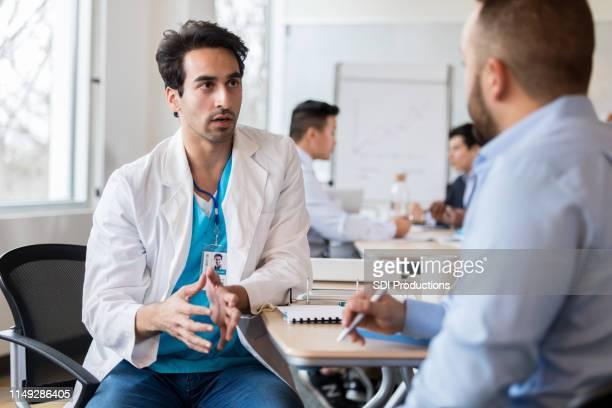 männlicher arzt spricht mit klinikadministrator - befragung stock-fotos und bilder