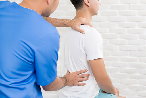 Male doctor therapist treating lower back pain patient in clinic or hospital 952969192