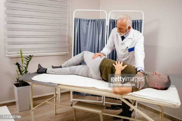 医院の患者の腰痛を扱う男性の医者のセラピスト - 下背部痛 ストックフォトと画像