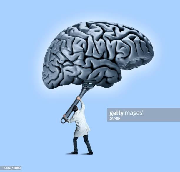 médico masculino usa chave grande para funileiro com cérebro acima dele - persuasão - fotografias e filmes do acervo