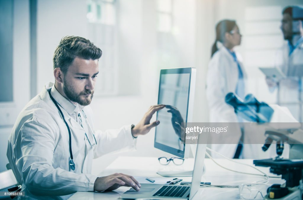 Male Doctor Using Computer With Colleagues Behind : Stock Photo