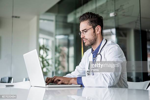 Male doctor using laptop at desk in clinic