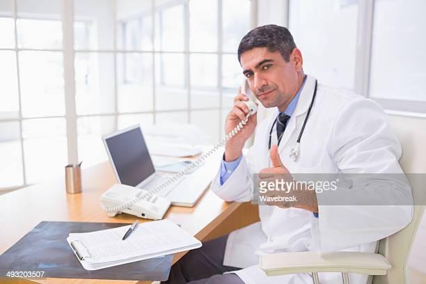 Homme médecin à l'aide de téléphone pendant gestes Pouce levé