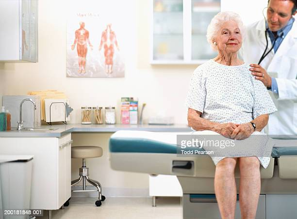 Male doctor using stethoscope on senior woman's back