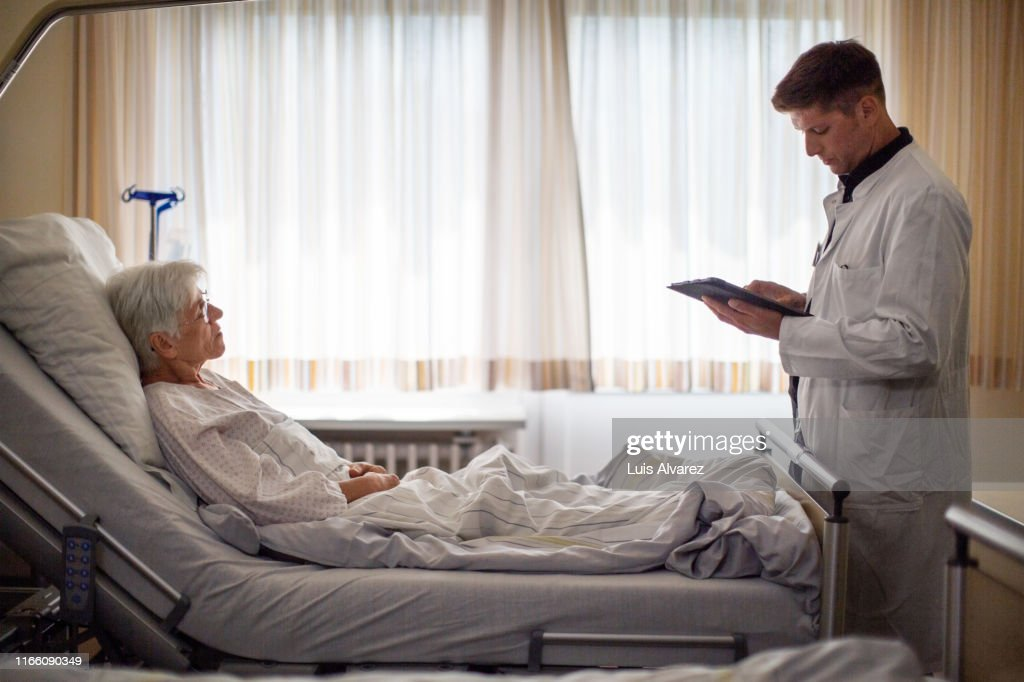Male doctor visiting senior patient in hospital ward : Stock Photo