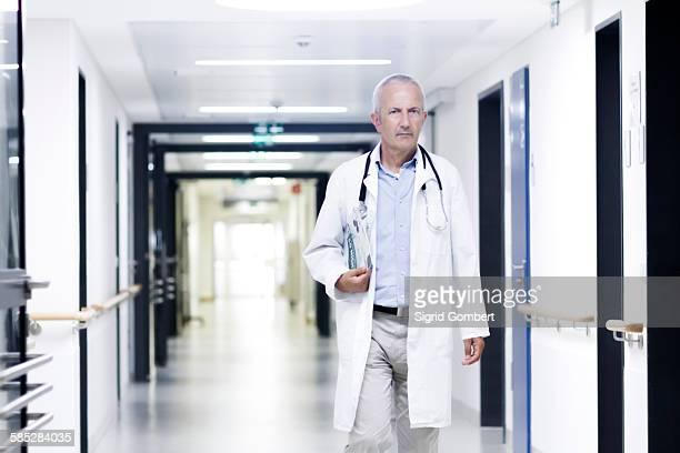 male doctor walking along corridor - sigrid gombert stock-fotos und bilder
