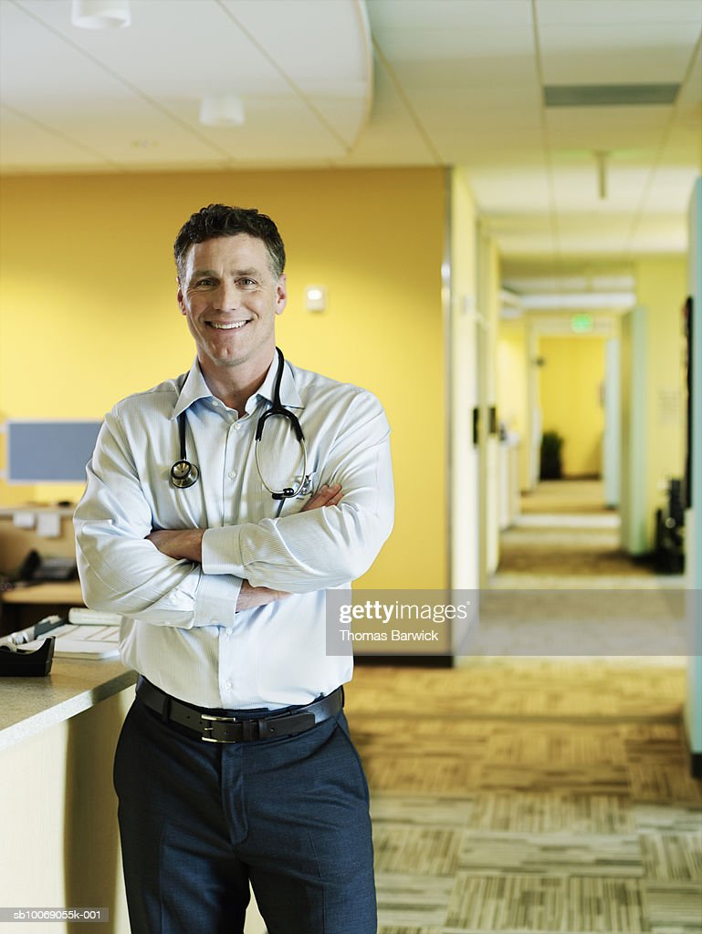 Male doctor with arms crossed, smiling, portrait : Stockfoto