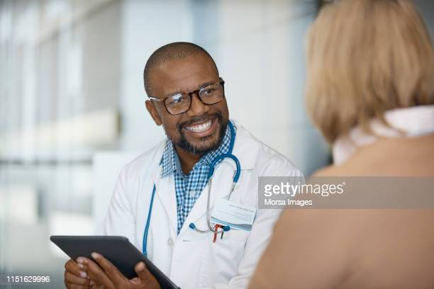 male doctor with digital tablet looking at woman - visit stock pictures, royalty-free photos & images
