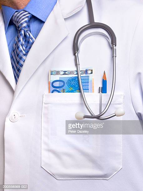 Male doctor with Euro notes sticking out of pocket, mid section