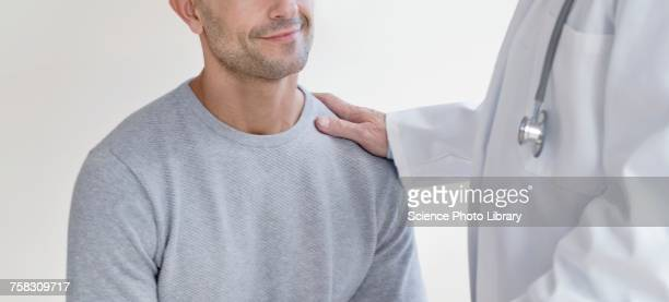 male doctor with hand on patients shoulder - hand on shoulder stock photos and pictures