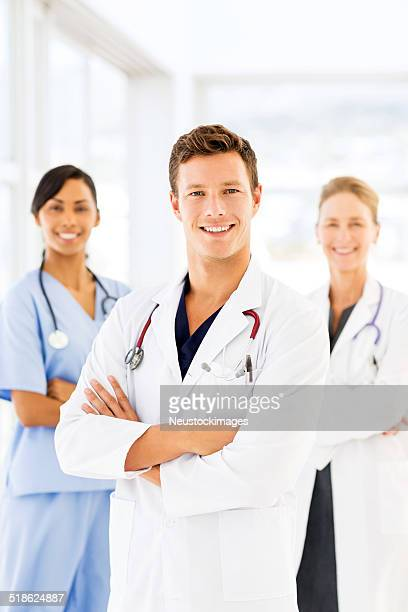 Male Doctor With Team In Hospital