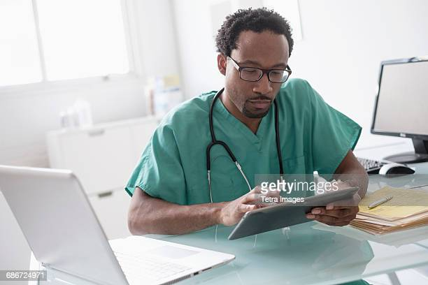 Male doctor working with digital tablet at desk