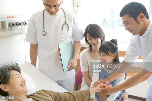 Male doctors and family visiting patient by bed