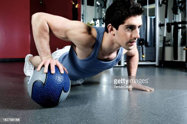Male doing  push up on  weight ball in a gym