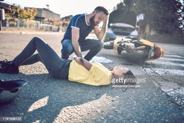 male driver devastated from car and scooter crash with female - motorcycle accident stock pictures, royalty-free photos & images