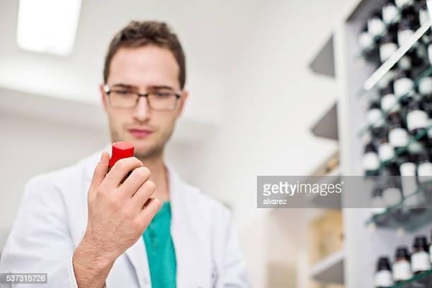 Homme votre droguiste vérifiant une bouteille de comprimés