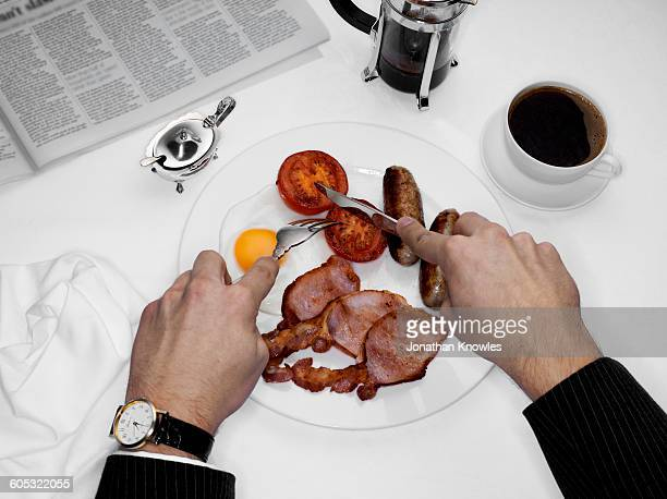 Male eating breakfast with newspaper on table