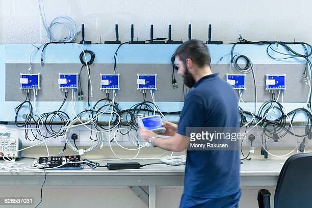 Male electrical engineer testing components in electronics factory