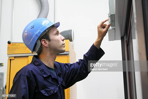 male electrician checking power control panel in factory - sigrid gombert stock pictures, royalty-free photos & images