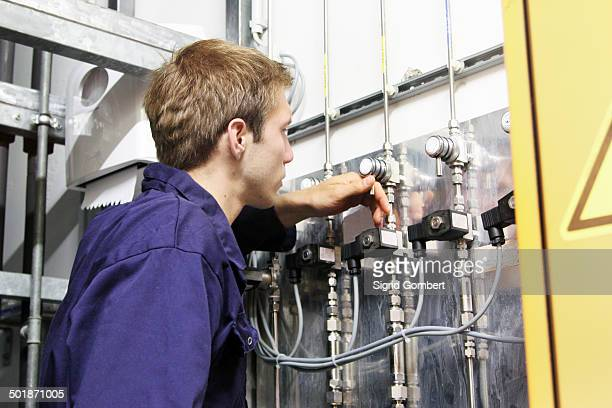 male electrician checking valves on power cables in factory - sigrid gombert stock-fotos und bilder