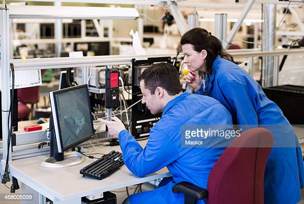 Male electrician pointing at computer monitor while discussing with colleague in industry