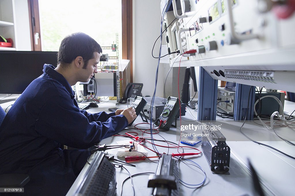 Male electrician repairing electronic equipment in workshop : Stock-Foto