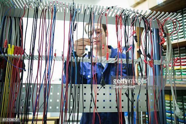 male electrician selecting power cable in workshop - sigrid gombert stock-fotos und bilder
