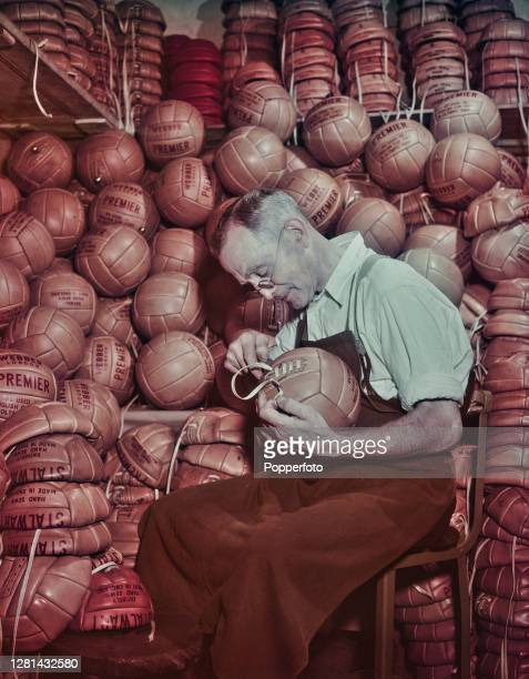 Male employee laces up leather Webbers footballs, branded Premier and Stalwart, at Webber Brothers ball factory in South Norwood, London in September...