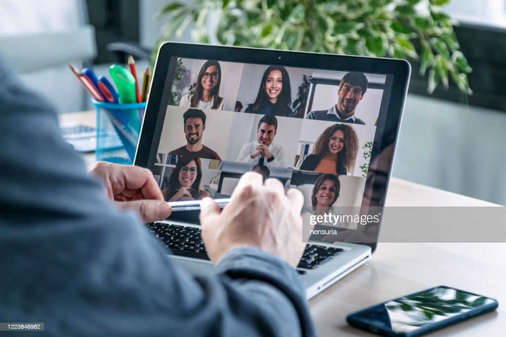 Male employee speaking on video call with diverse colleagues on online briefing with laptop at home. : Stock Photo