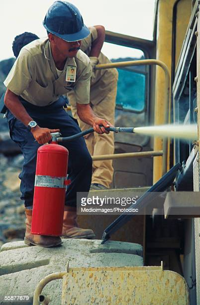 Male employee using fire extinguisher