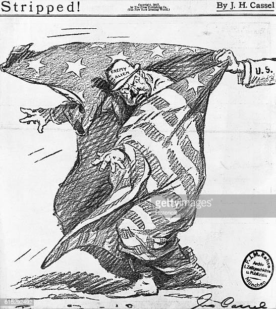 A male enemy alien is about to have the American flag he is wrapped in pulled away as a symbol of his cloak of American citizenship being ripped away...